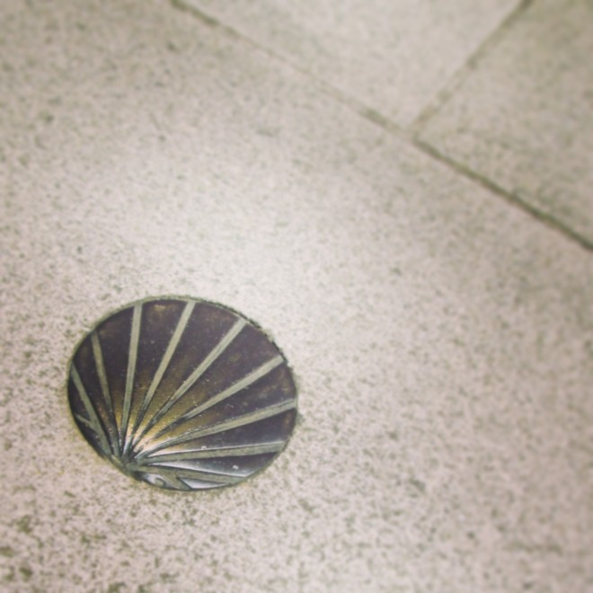Bronze scallop shell marker embedded in the pavement as one enters Santiago de Compostela