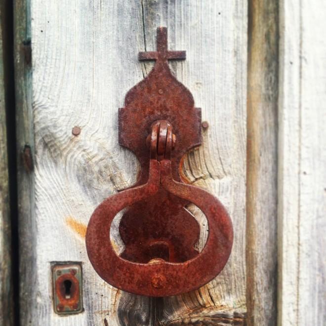 Door handle on a barn door, opposite a chapel